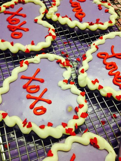 Violet covered heart cookies with red and white decoration