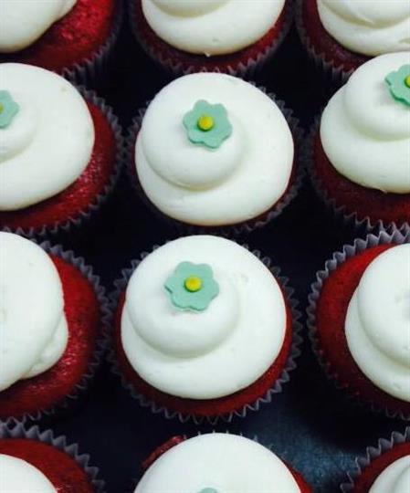 Cupcakes topped with white frosting and green sugar flowers
