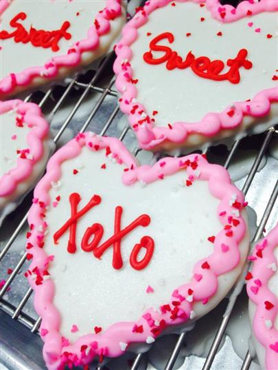 White covered cookies with pink decoration and red letters