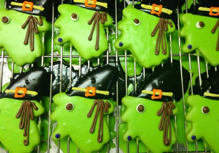 Light green covered cookies topped with chocolate hats and funny decoration
