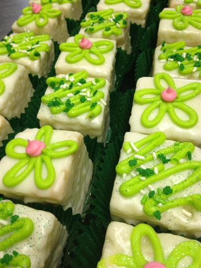 Cream mini cakes topped with light green and pink decoration