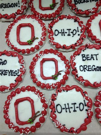 White covered cookies topped red decoration and chocolate letters