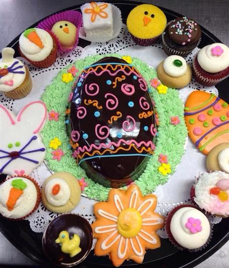 Platter with a chocolate easter egg surrounded of several colorful cookies and cupcakes