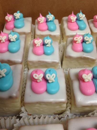White mini cakes topped with a pink and a blue sugar baby shoe