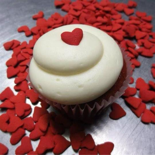 Cupcake topped with white frosting and a red heart