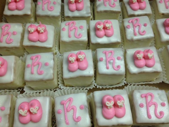 Mini cakes topped with white topping, and pink decoration