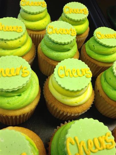 Cupcakes with yellow frosting topped with light green sugar and yellow letters