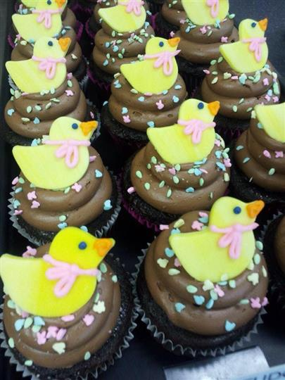 Cupcakes with chocolate frosting topped with little yellow sugar ducks