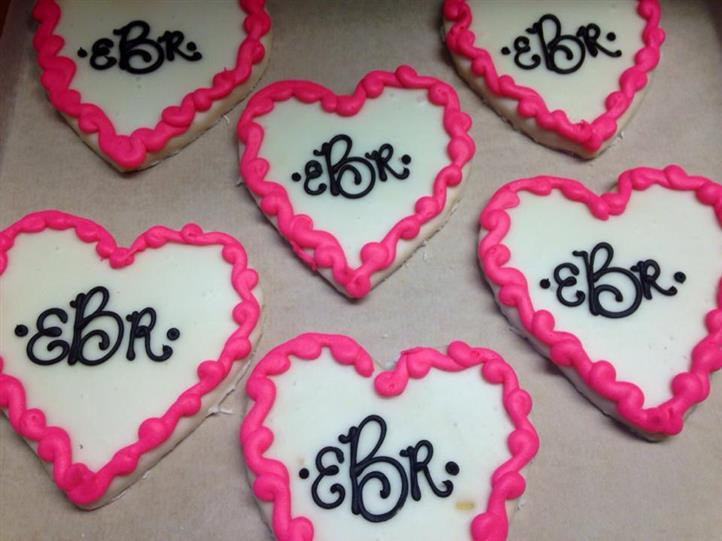 White and pnk cookies in heart shapes topped with chocolate letters