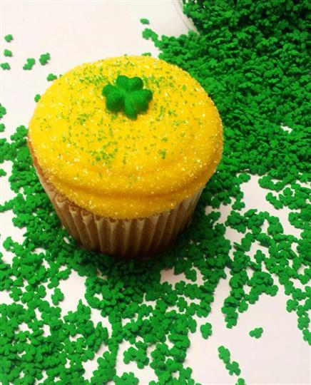 A cupcake with yellow frosting and a green clover on top