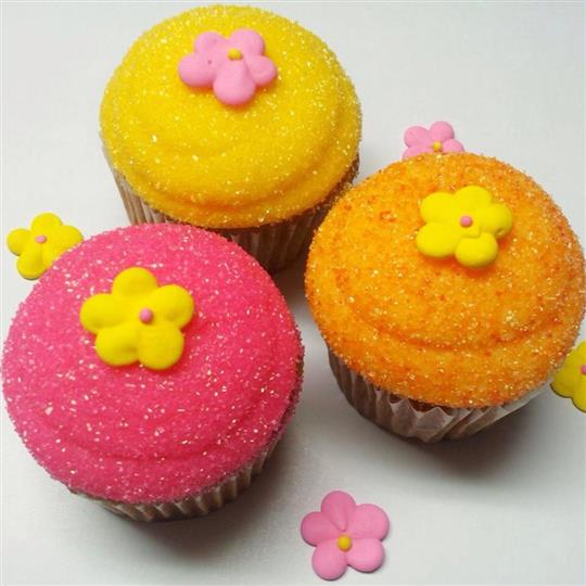 Three cupcakes with different frostings (yellow, pink, and onange) topped with sugar flowers