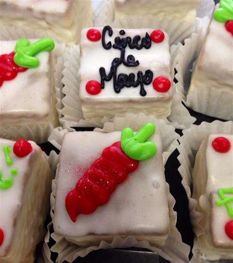 White mini cakes topped with red decoration and chocolate letters