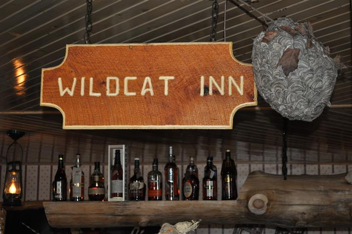 """wooden sign that reads """"Wildcat Inn"""", above a shelf of alchoholic beverages"""