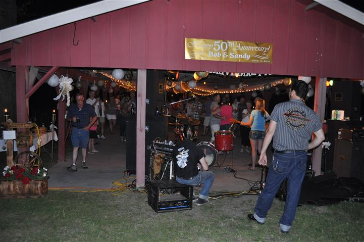 a barn area with lighting, decorations, and a live band