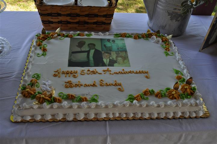 """a decorated cake that reads, """"Happy 50th Anniversary Bob and Sandy"""""""
