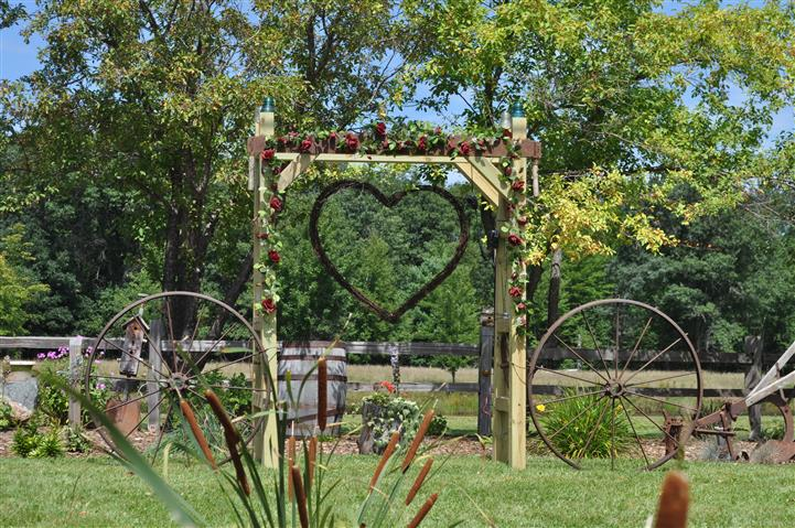 a metal heart structure hanging from a wooden frame