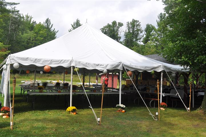 a large tent covers several dining tables outdoors