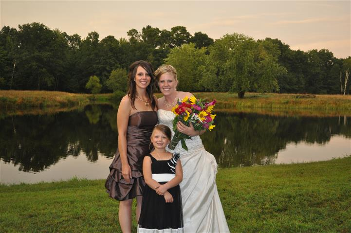 a bride and her family posing near a lake