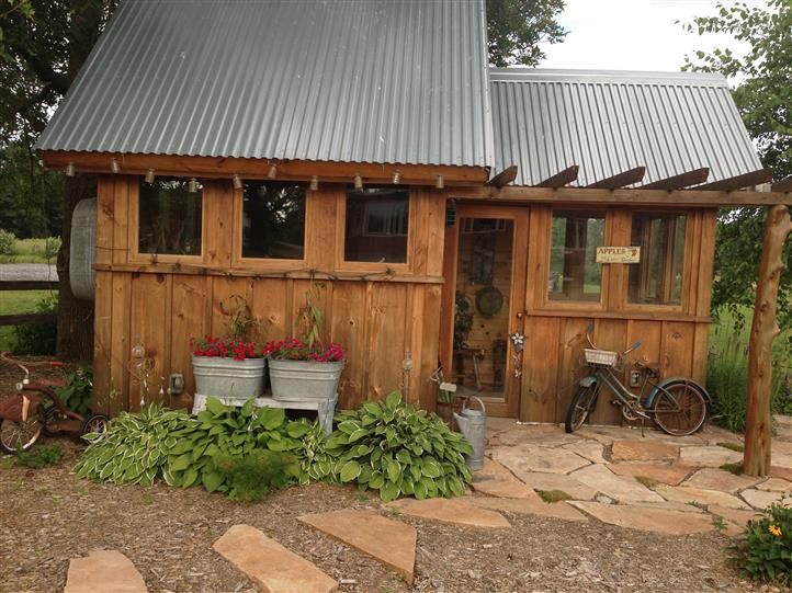 a small wooden shed with a nearby garden