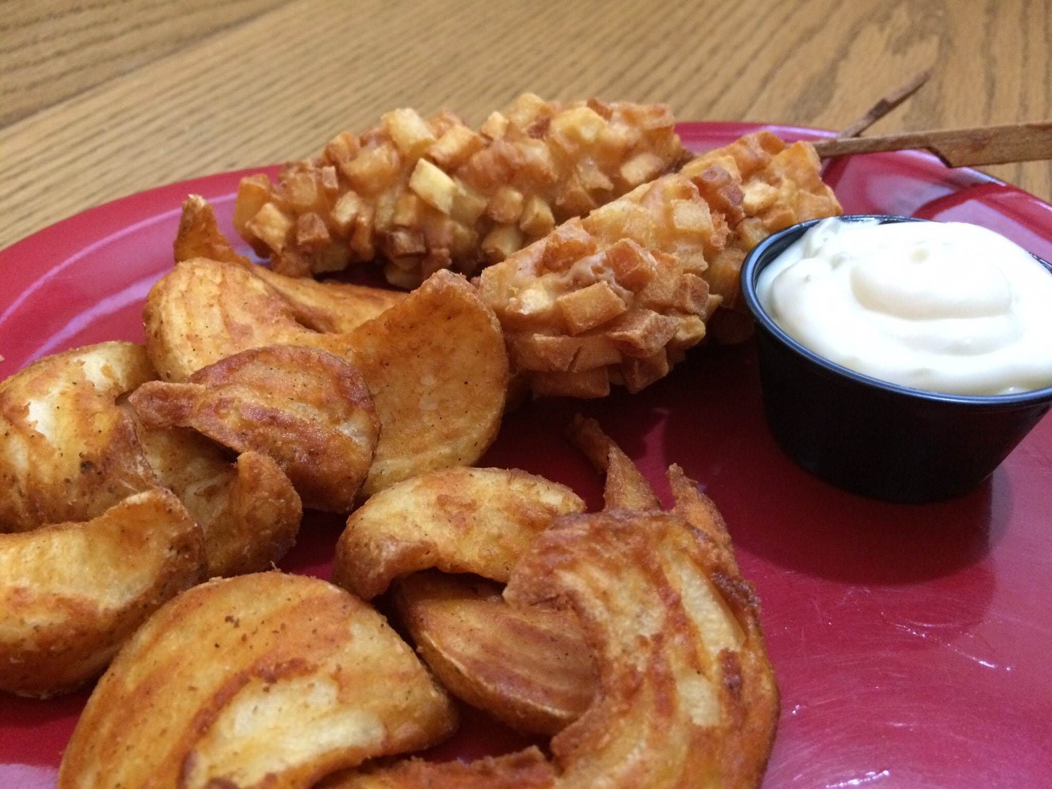 fried potatoes on a plate with a side of dipping sauce
