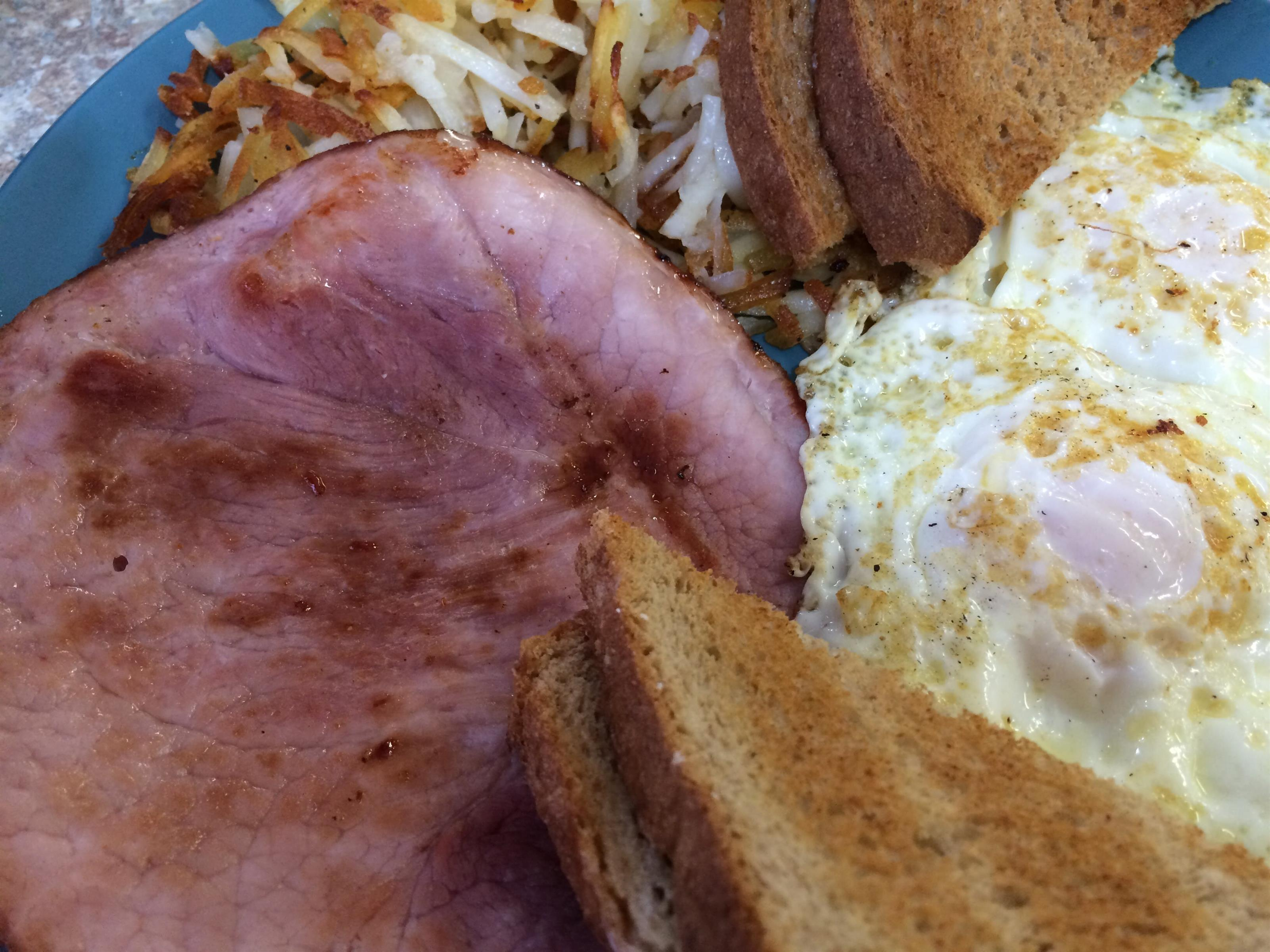 ham with toast, hash browns, and eggs on a plate