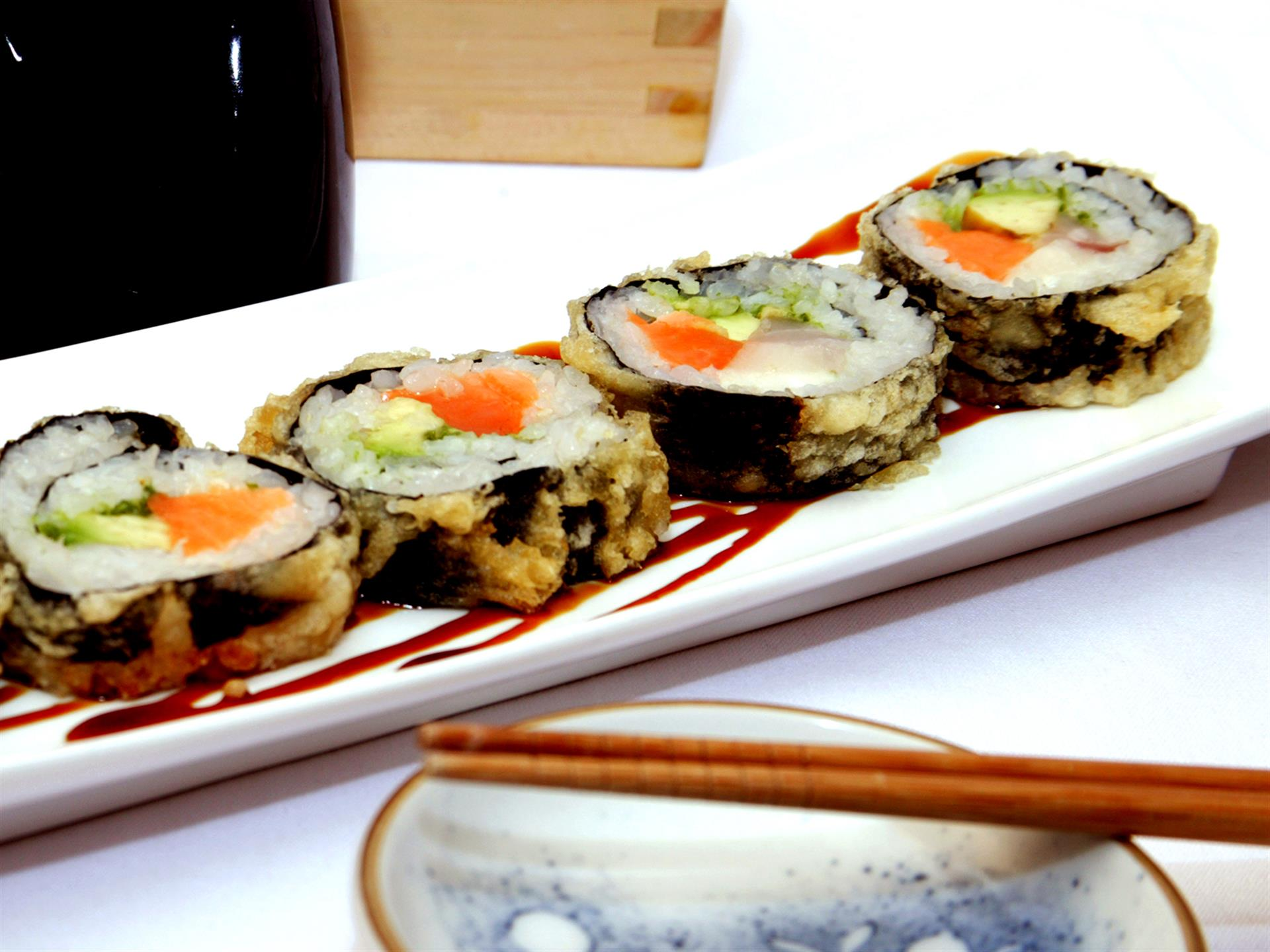 sushi rolls lined up on a plate