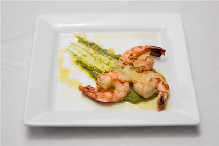 shrimp on a square plate with decorative sauce