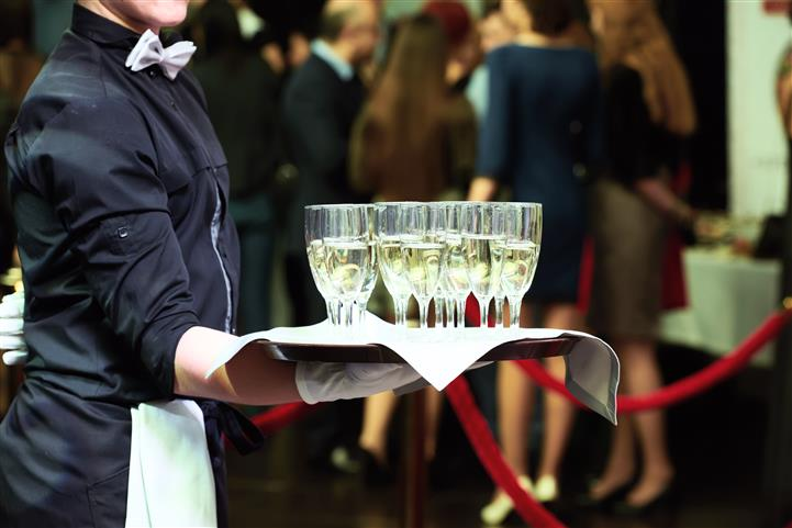 Waiter Holding Glasses with champagne in them