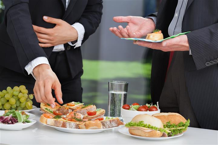 People in suits taking food
