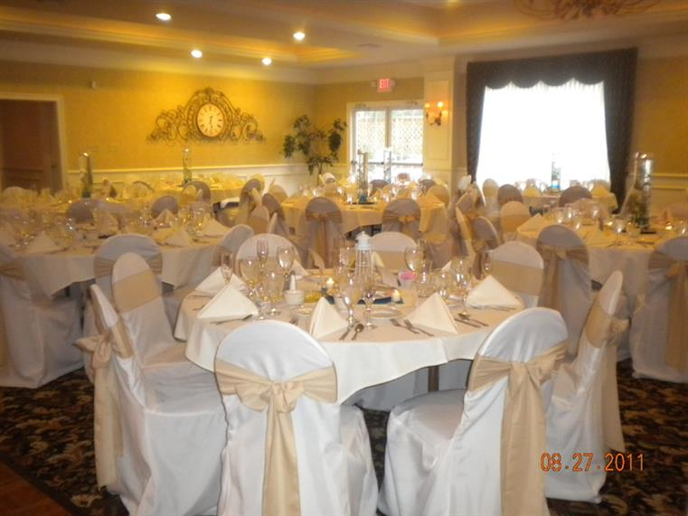 Dining tables covered in white cloths with white clothed chairs.
