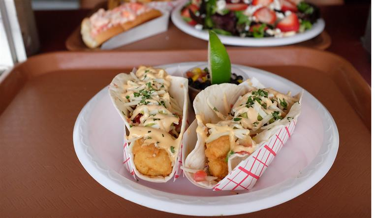 fish tacos in a basket with a lime wedge