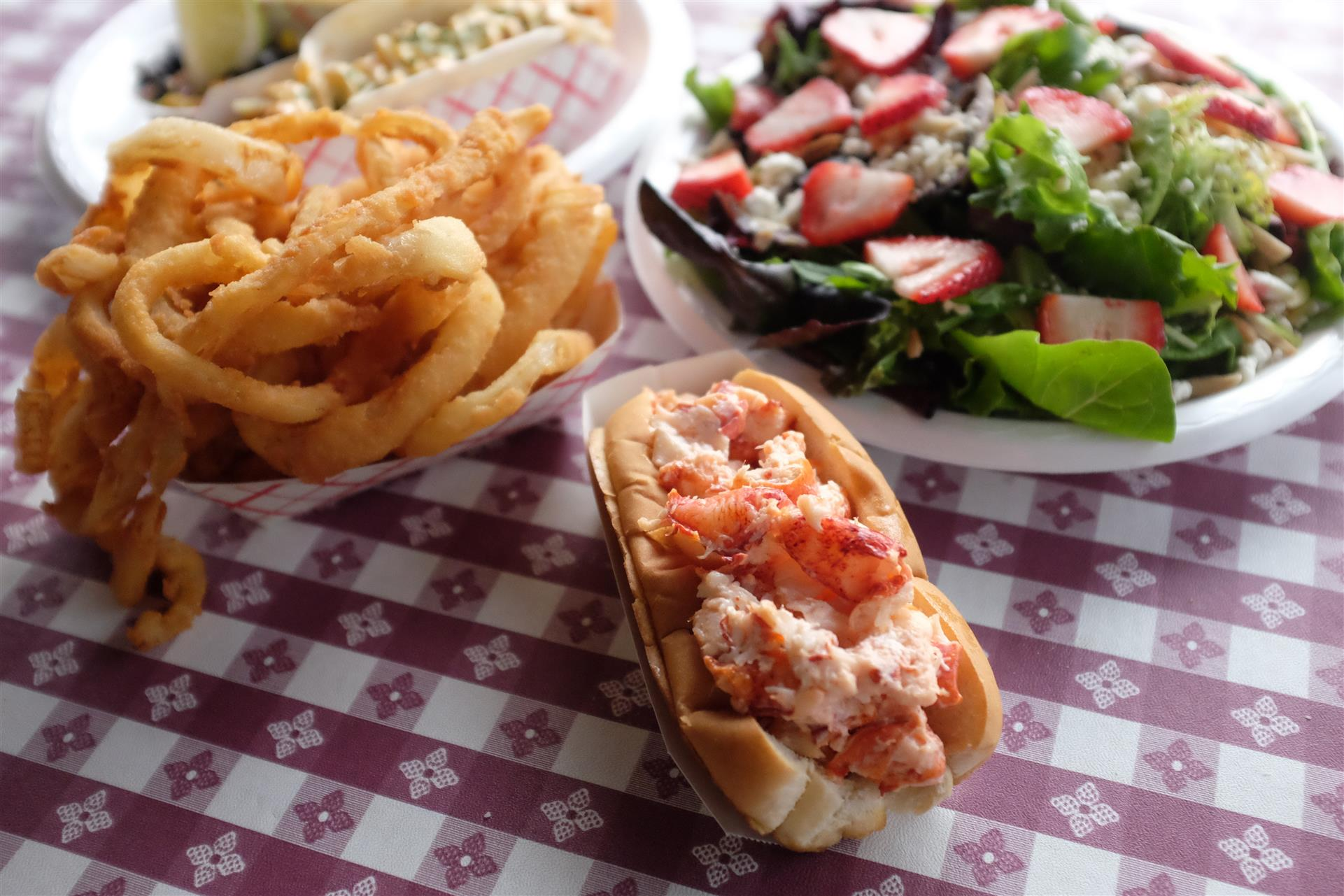 lobster roll with a side of onion rings and a strawberry salad