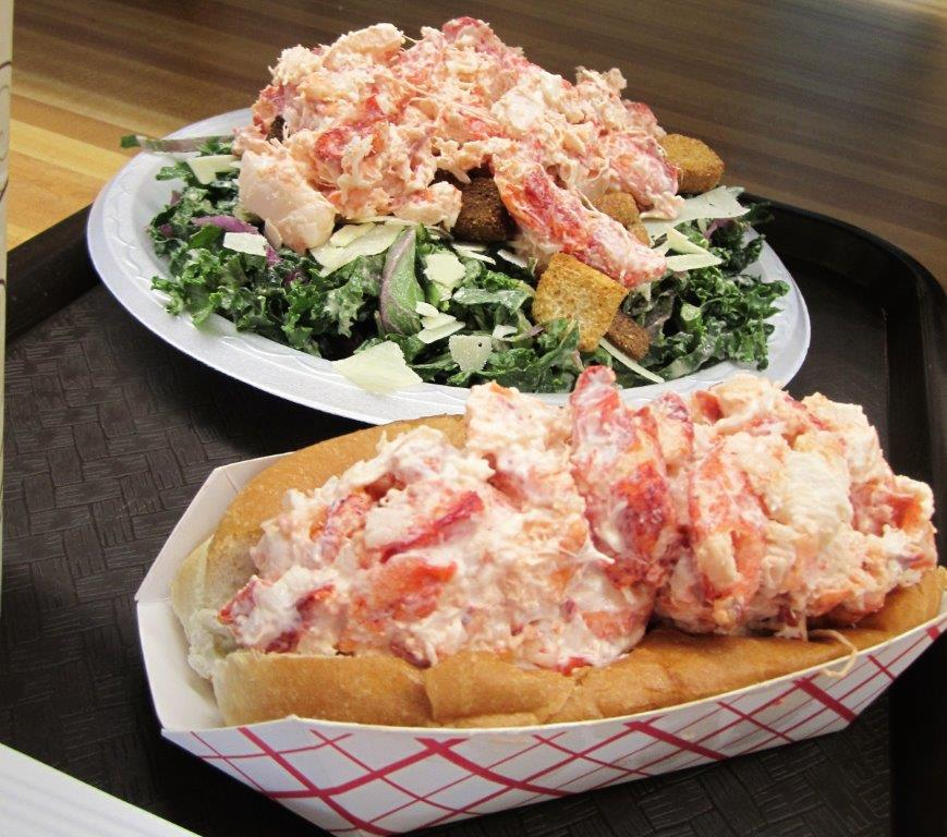 lobster roll and a caesar salad topped with lobster on a tray