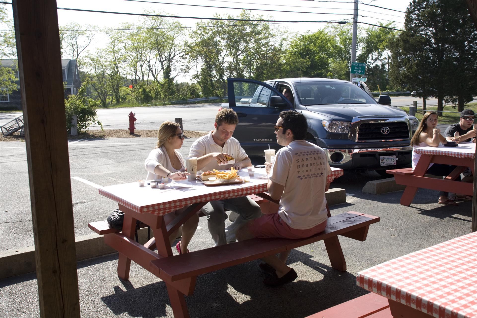 three people sitting at a picnic table