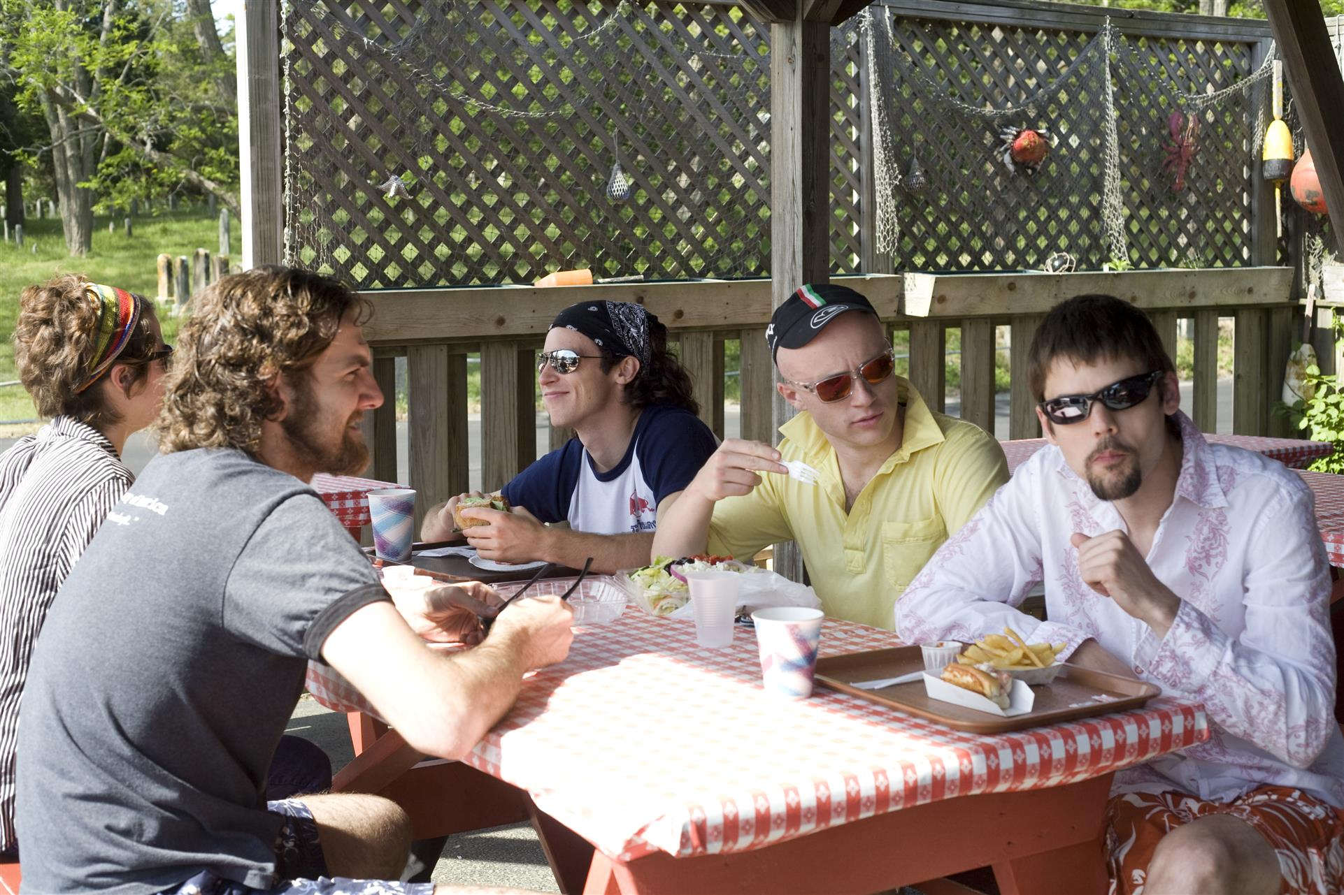 a grouo of men eating at a picnic table