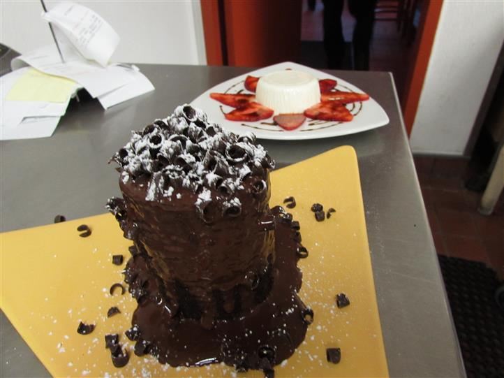 A chocolate tower dessert next to a white pudding plate with sliced strawberries