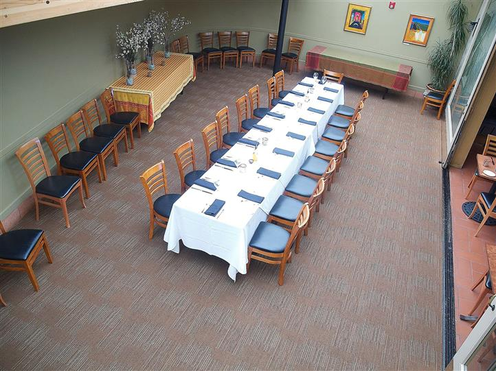 Interior shot of the restaurant with a long table decorated with table sets
