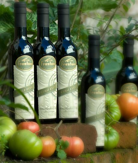 Bottles of Frantoio olive oil surrounded by fresh tomatoes