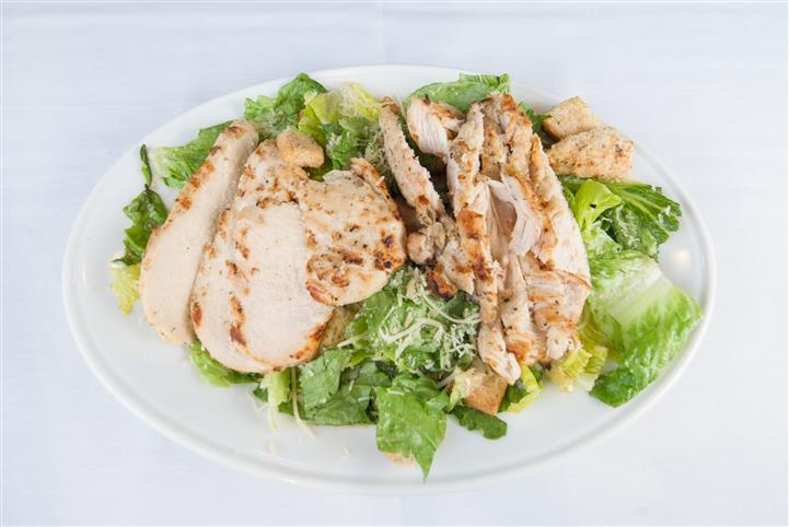 Salad topped with cheese and grilled chicken salad
