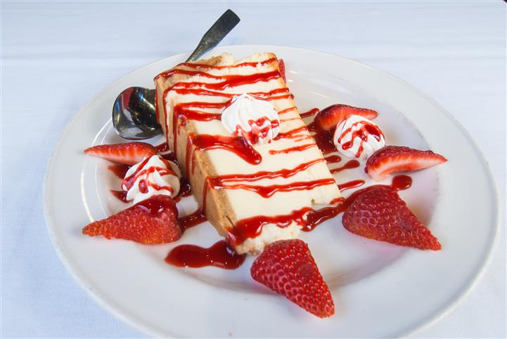Cheese cake topped with strawberry syrup. Along with a side of sliced strawberries