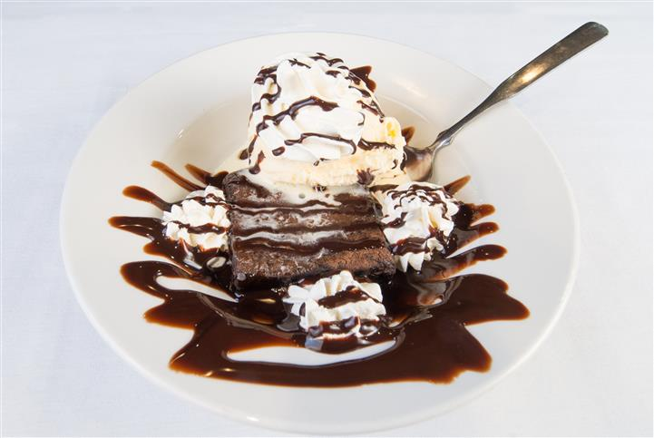 Brownie topped with ice ream and chocolate syrup