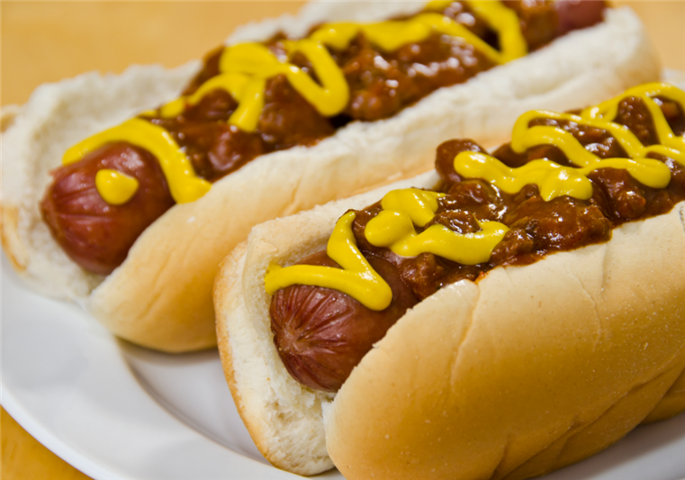 Two hot dogs in buns with mustard and chili on top