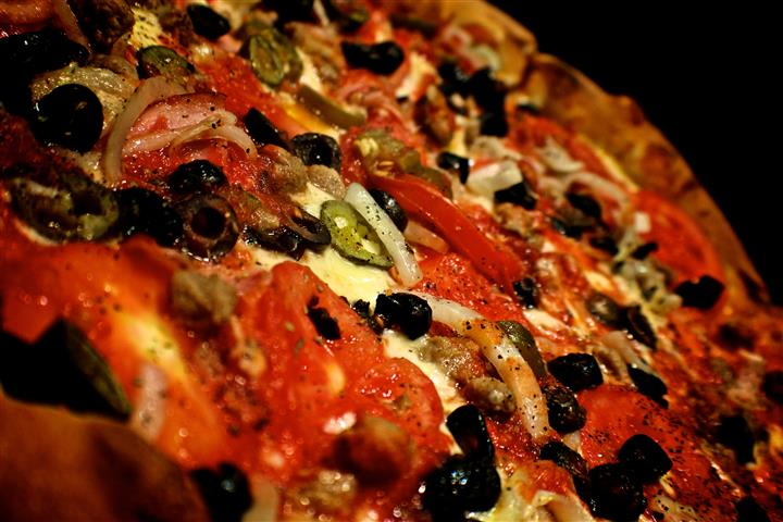 Pizza with olives, peppers, tomatoes, cheese, onions