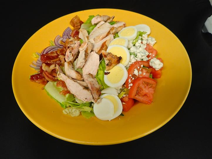 a cobb salad with boiled egg, bleu cheese crumbles, tomato, chicken, bacon, and red onion on a bed on lettuce on a yellow plate