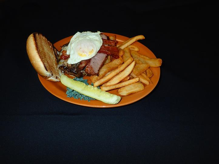 a burger with an egg over easy with a side of fries and a pickle on an orange plate