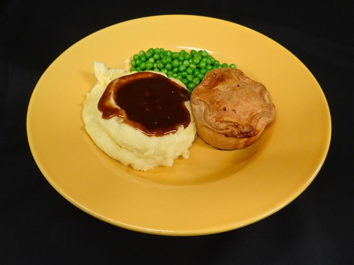 a side of mashed potato and gravy, peas, and a biscuit on a yellow plate