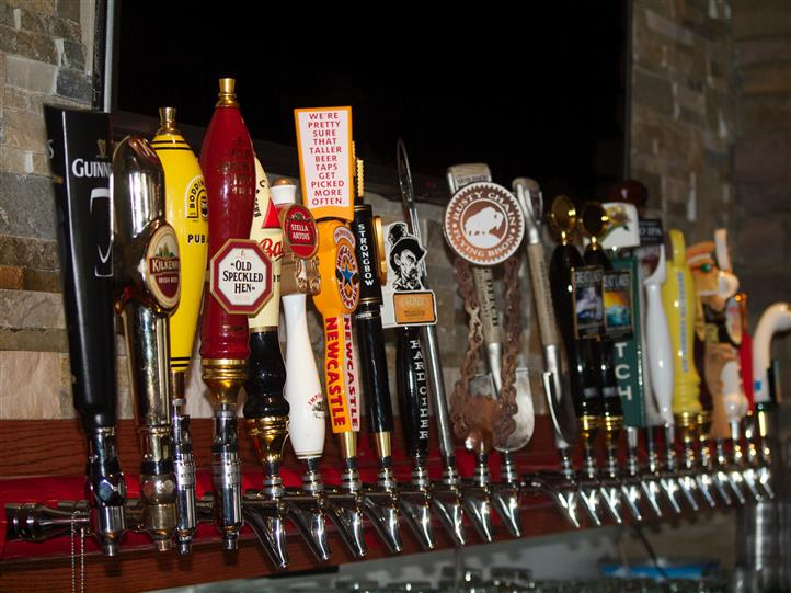 a row of beer taps at the bar