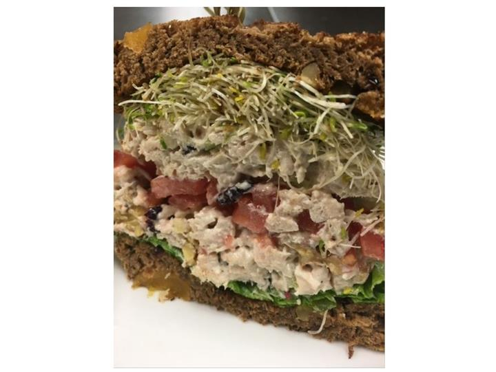 Tuna salad sandwich with sprouts and tomatoes on rye