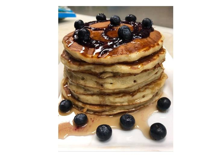 Stack of pancakes with blueberries and syrup.