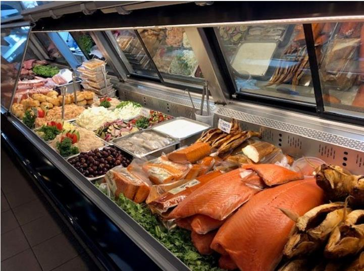 Deli case with assorted fish, vegetables, and spreads